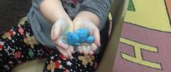 Student holding blue slime in hand