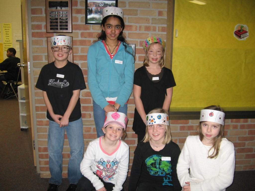 students pose for camera wearing crowns they made