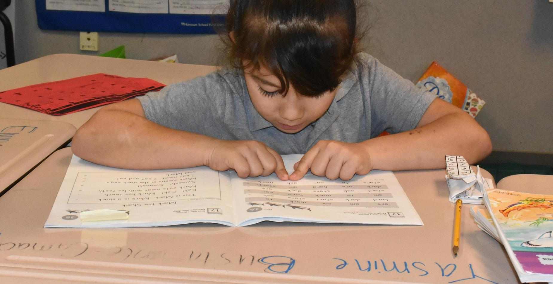 A girl reading in reading group, tracking with two fingers.