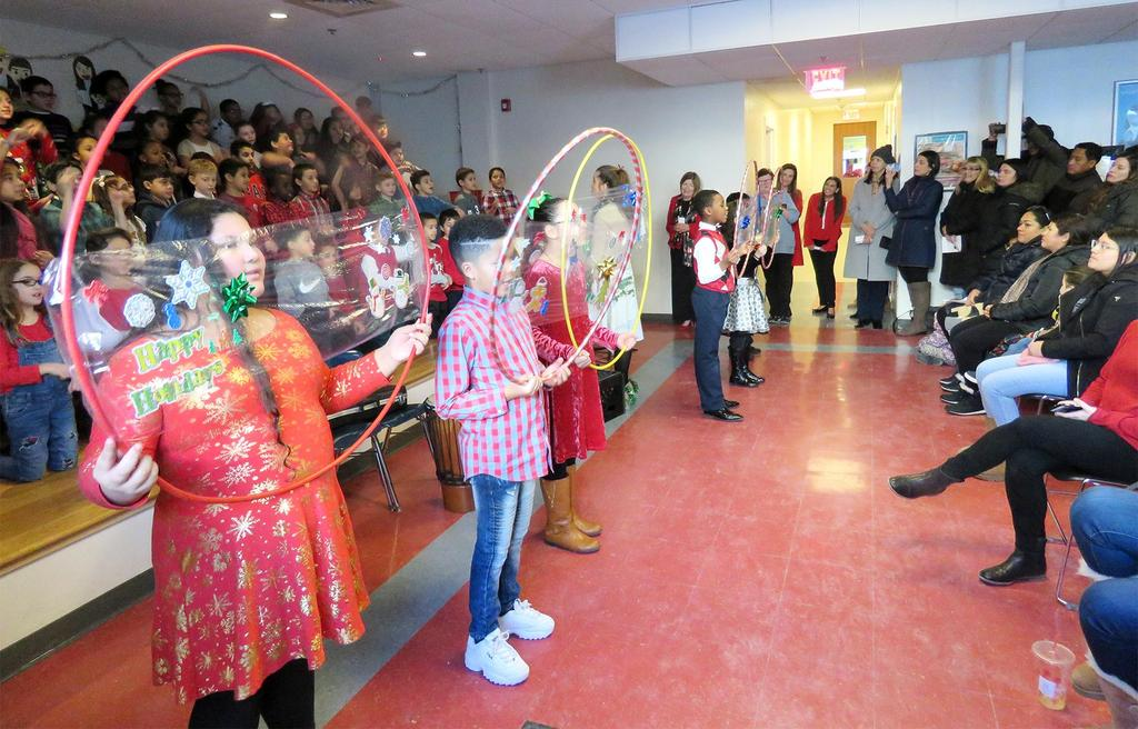 Students dance with hula hoops with holiday decorations