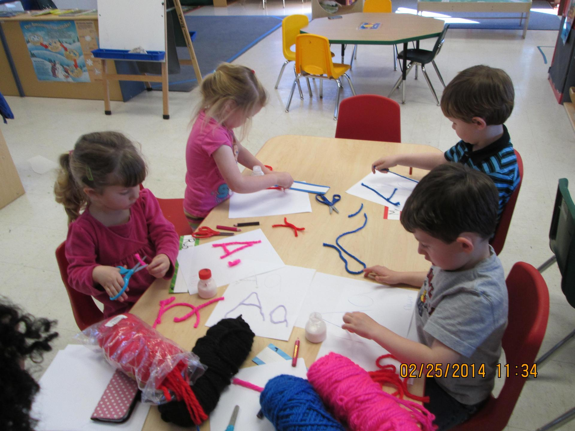 children building letters with pipe cleaners