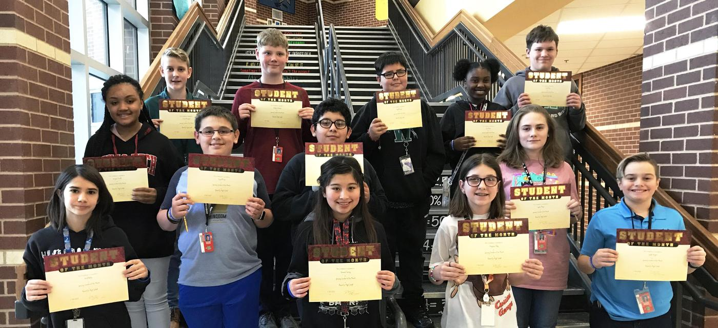 group of 13 students pose on steps with student of the month certificates