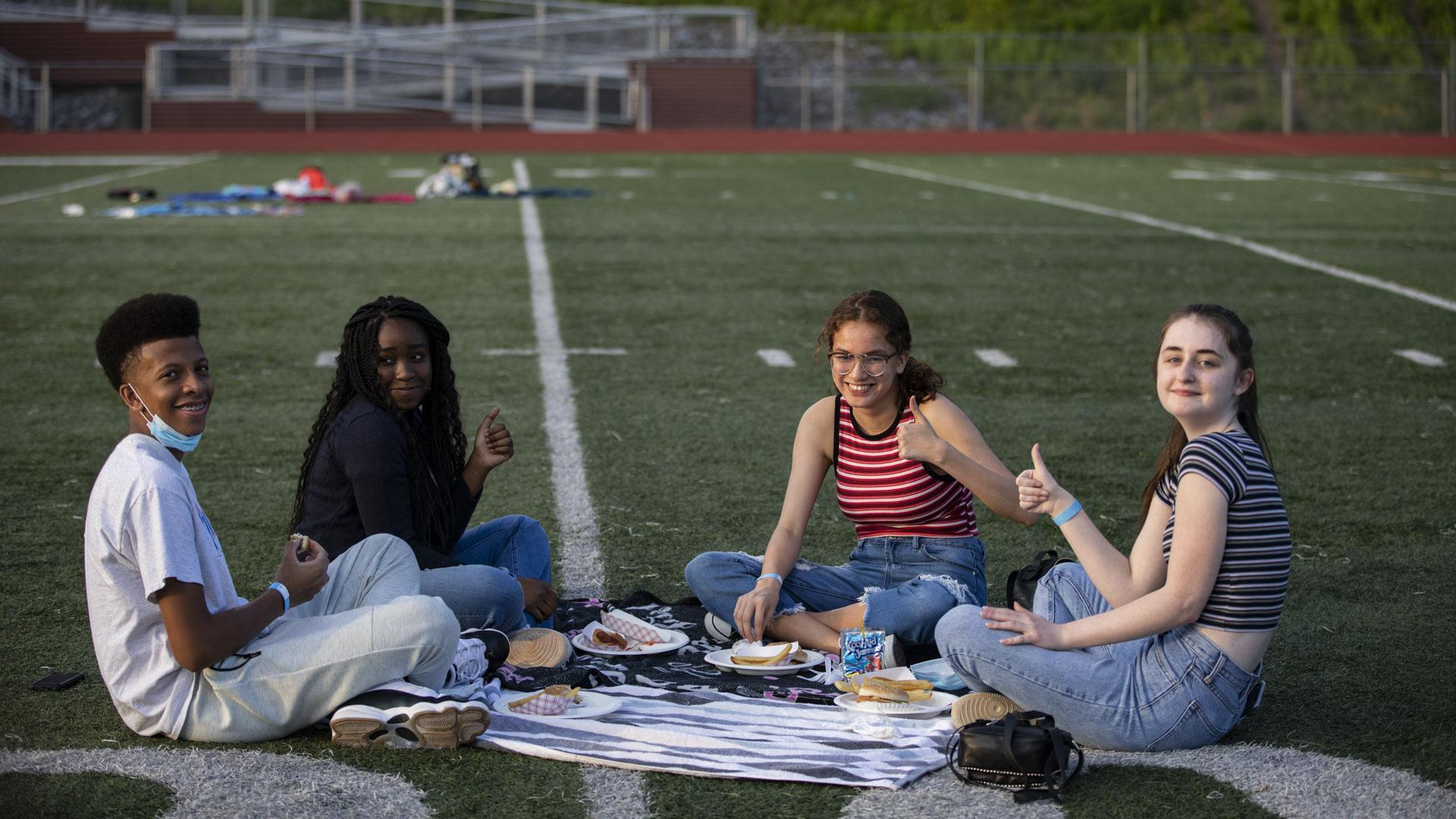 Students picnicking on football field