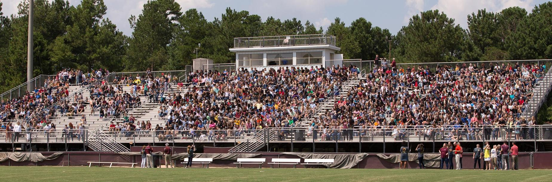 students in the stands at the football stadium