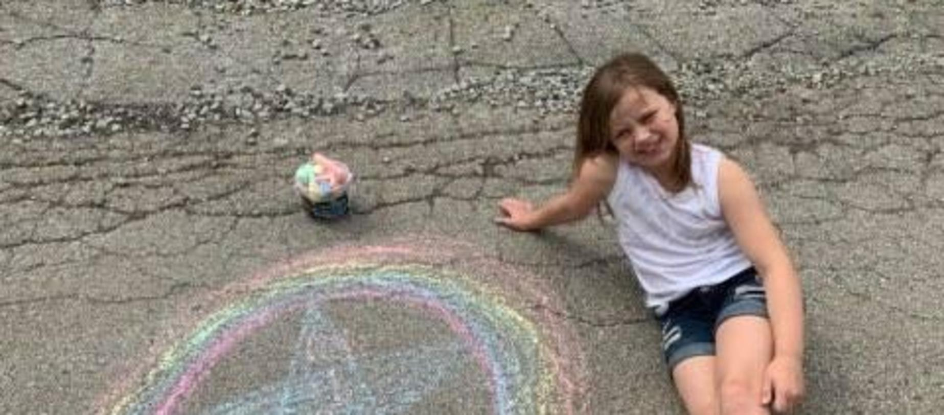 girl sitting on driveway playing with sidewalk chalk