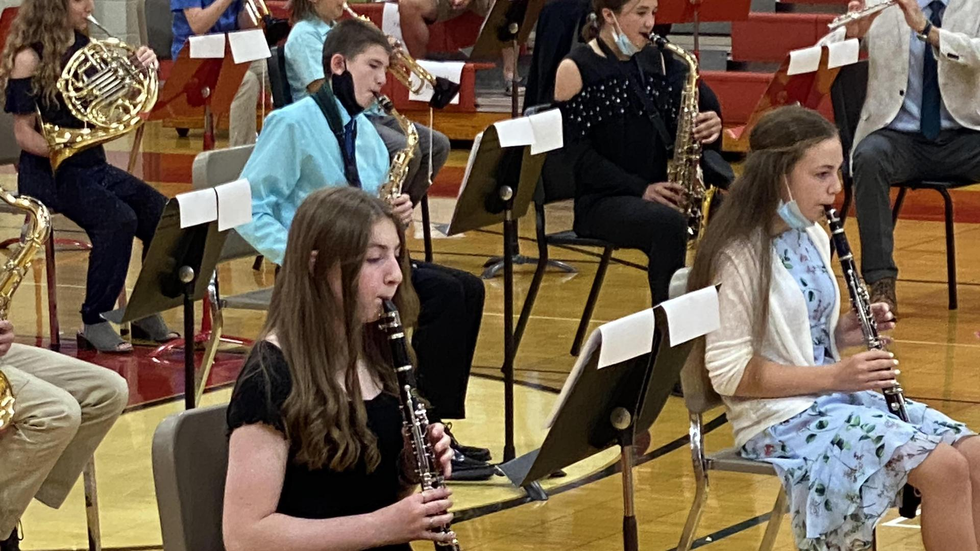 Students playing instruments in the Benjamin gym. The focus is on a clarinet player. Another clarinet player and a saxophone player can be seen clearly in the background.