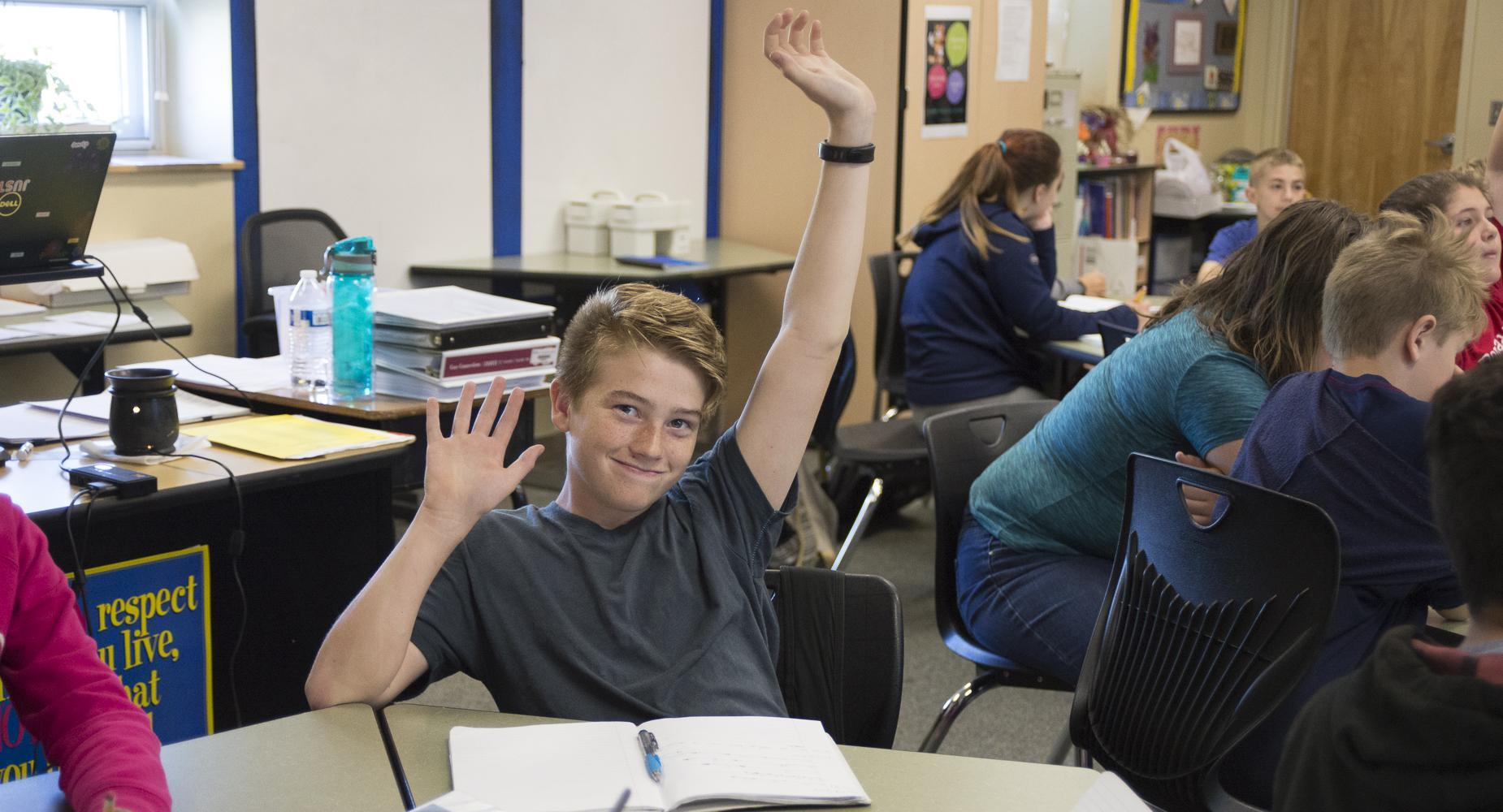 Boy raises his hand in class