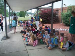 Students and staff are on the sidewalk for dismissal.