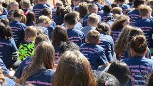 Students sit on the grass in matching school T-shirts during the ribbon-cutting ceremony.