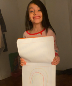 Girl holding notebook with rainbow drawing
