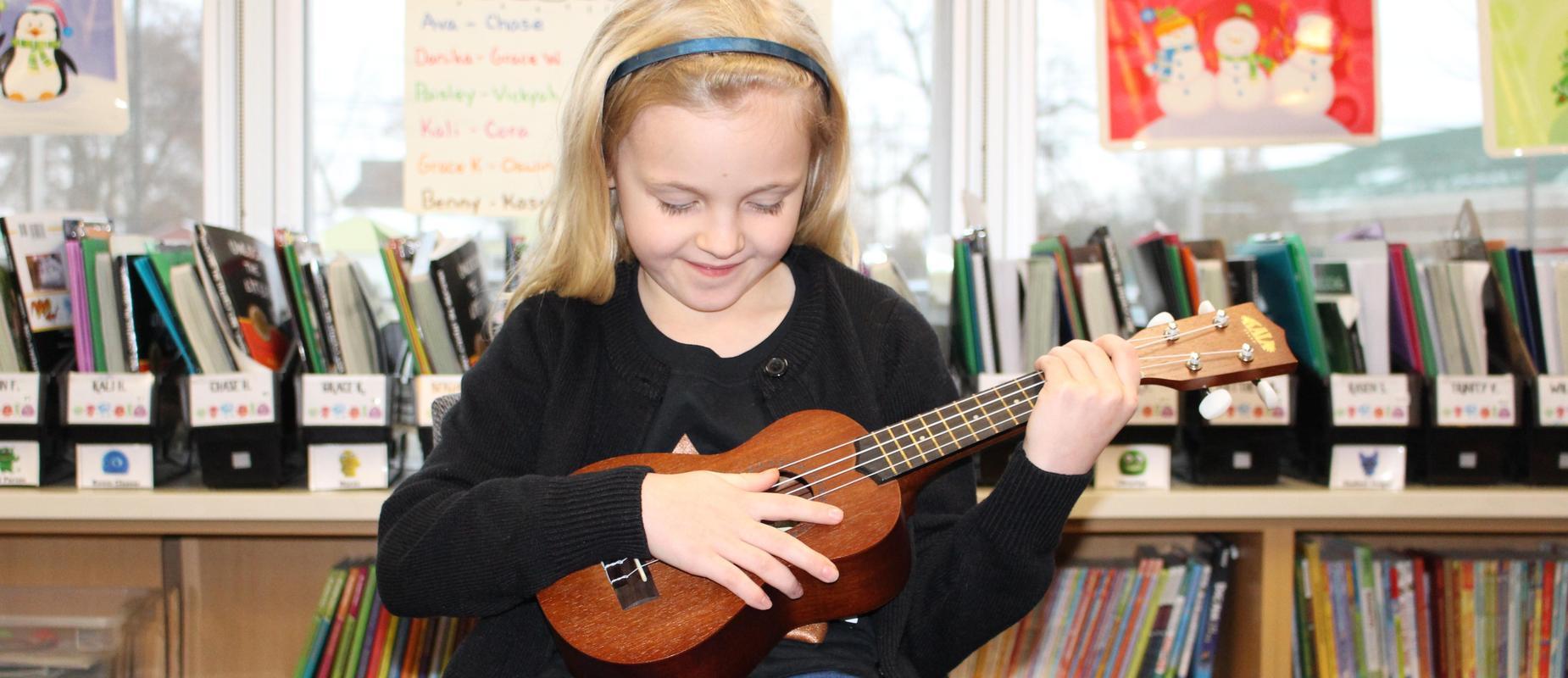 girl playing ukulele in classroom