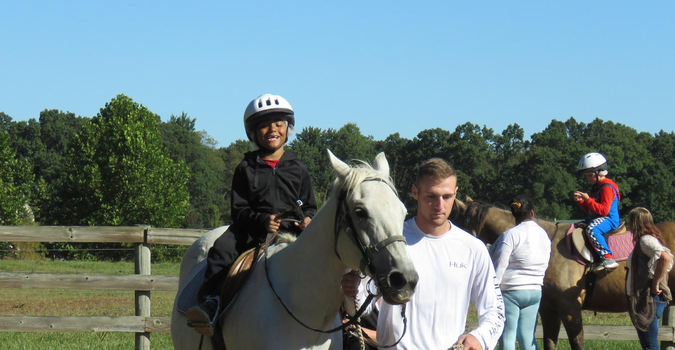 A McFall student is all smiles as he enjoys a therapeutic horse riding lesson.