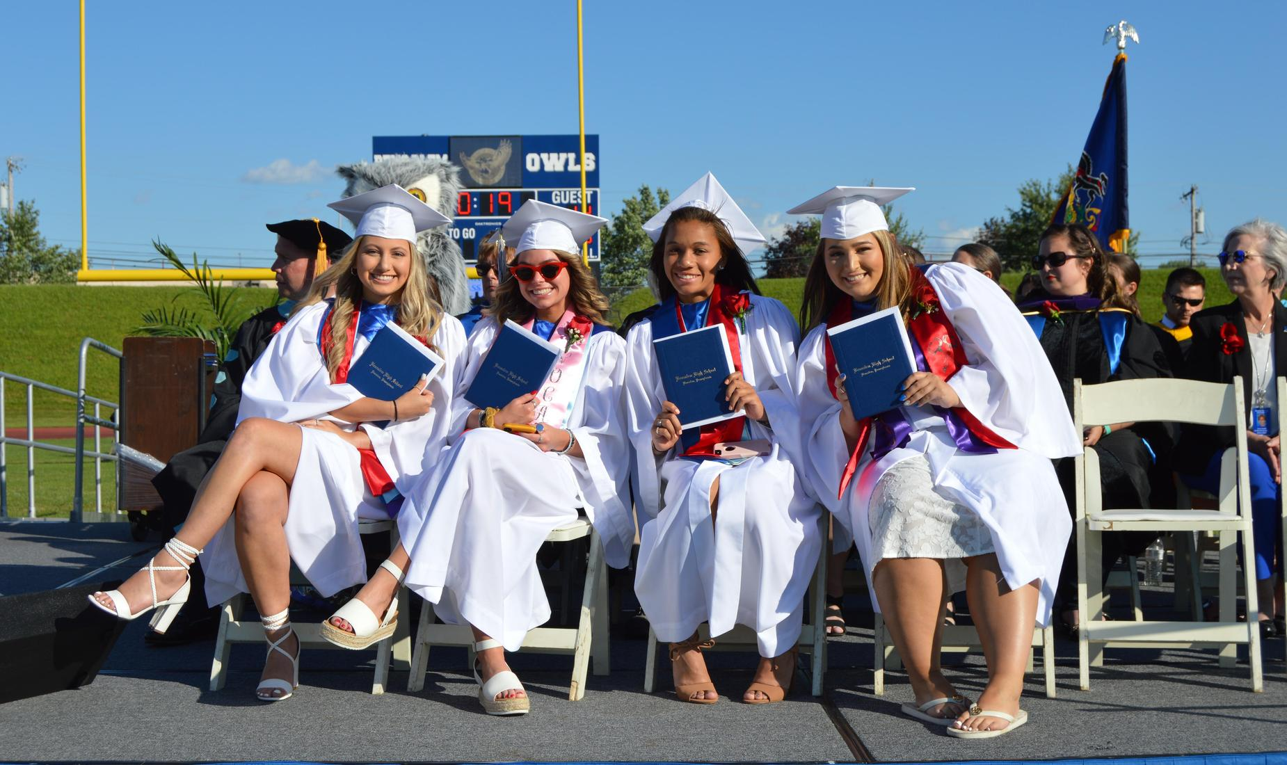 Student Government Officers dresses in white graduation gowns hold up their diplomas