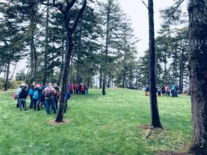 Student's arriving at outdoor school, in an open field with trees in the background.