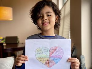 Miguel holding his kindness heart drawing