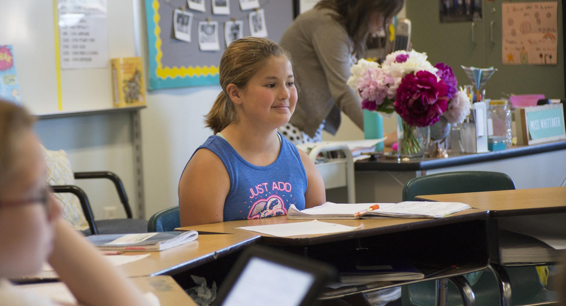 Girl sits at desk with teacher's flowers in the background.