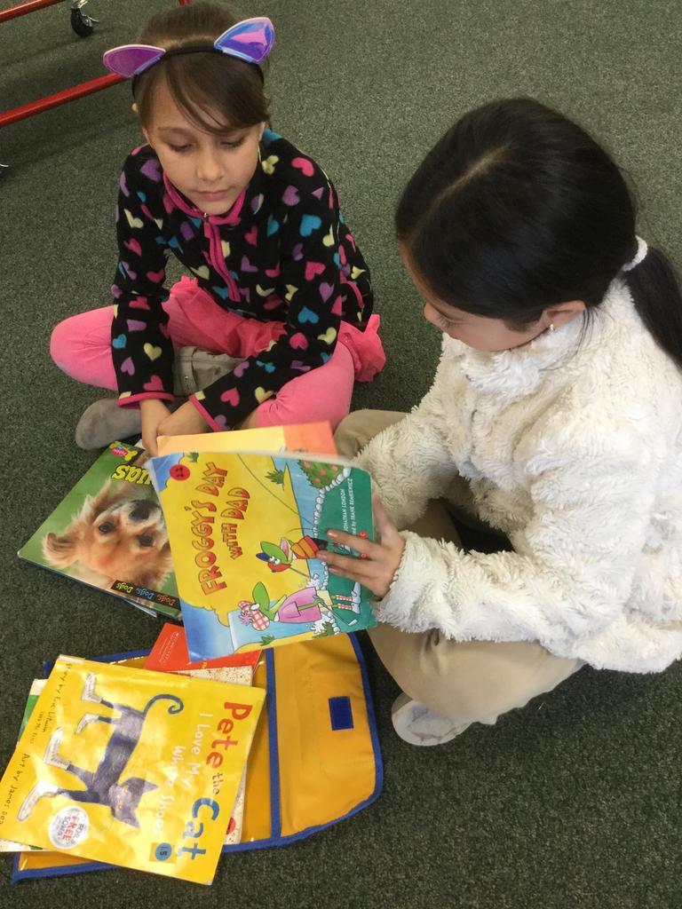 kindergarten student shows book to third grade student