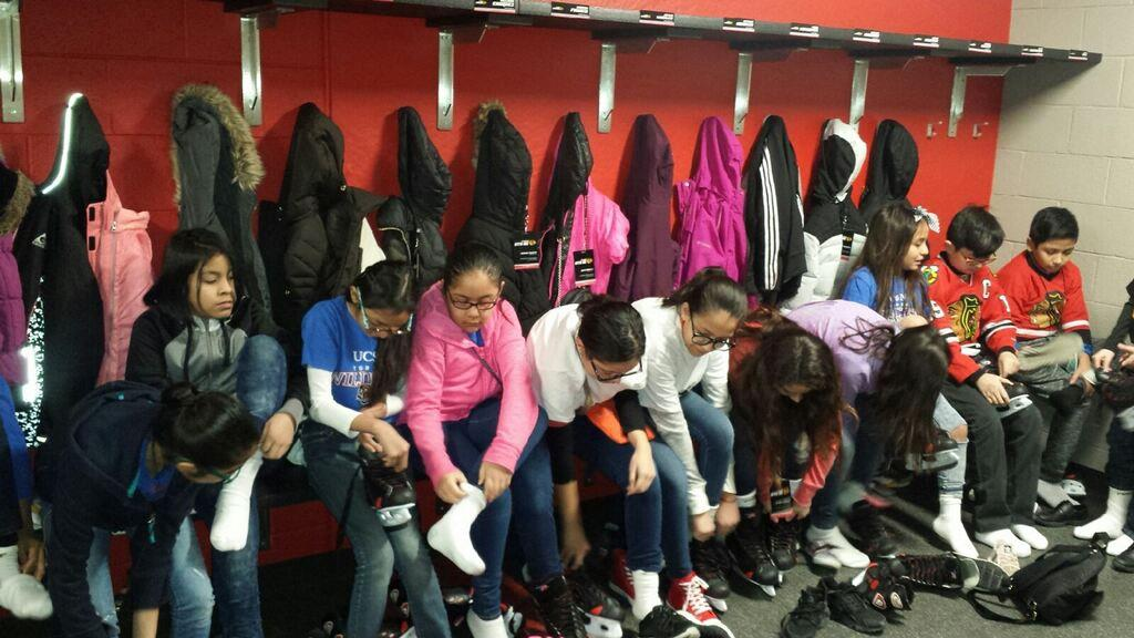 Torres students sit on bench to put on ice skates