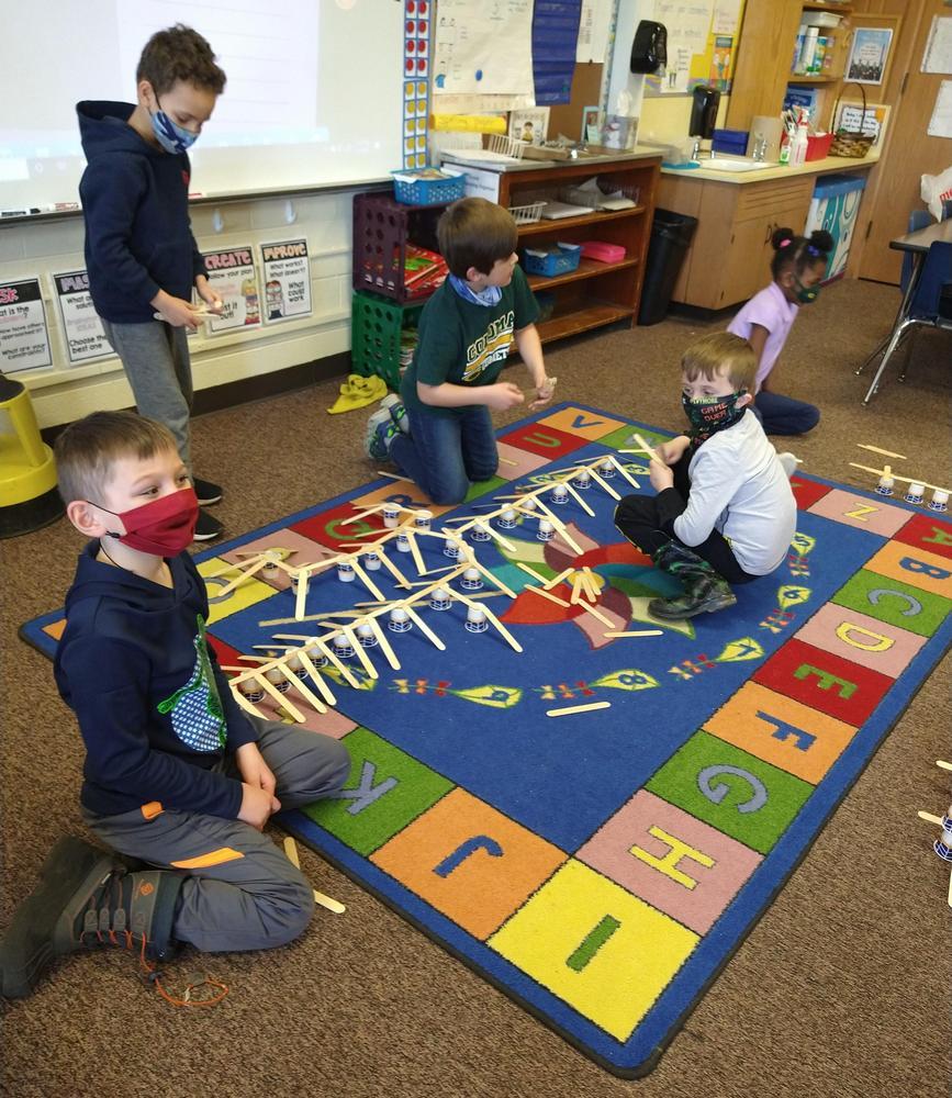children building craft stick bridges