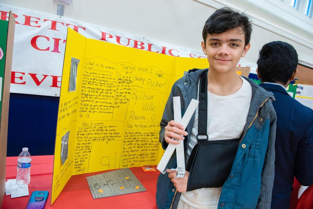 A student holds his project, The Sticky Picker