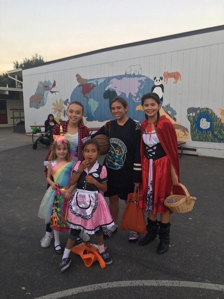 children dressed in haloween costumes - unicorn, little red riding hood, lumber jack, shark, waitress