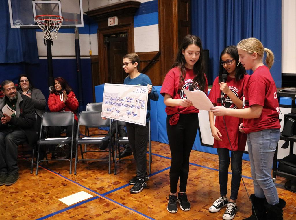 Photo of three Wilson students announcing and one student holding representative check indicating amount raised for the Special Olympics during Month of Hope.