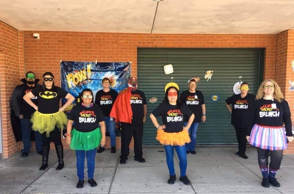 large group wearing superhero costumes