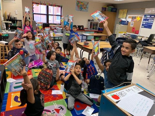 group of student in their classroom with their backpacks holding up books