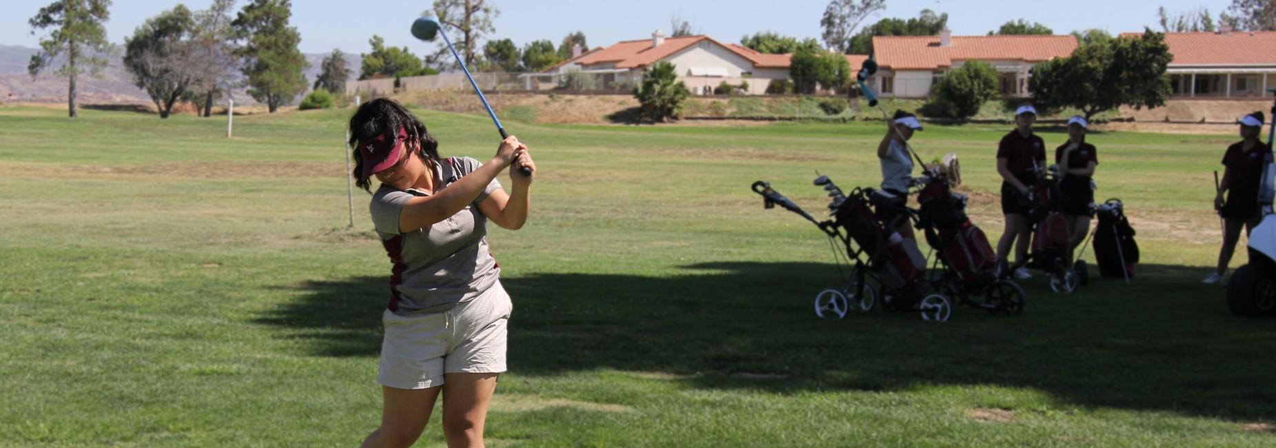 Girls golf team player hitting the ball