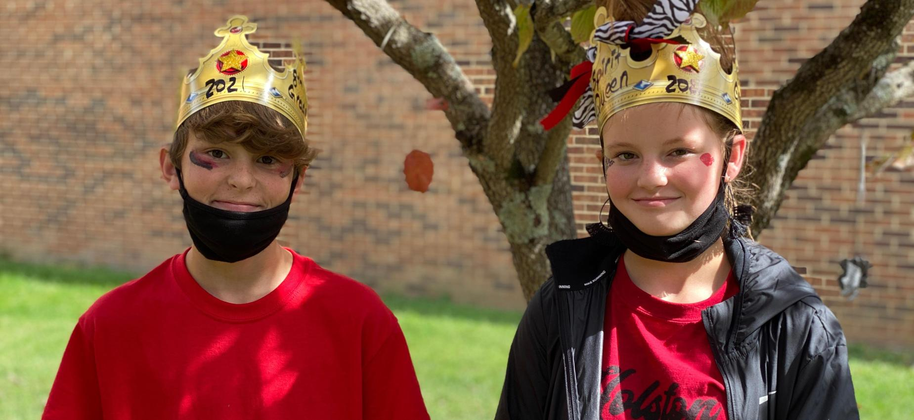 Two students wearing crowns stand outside a school.