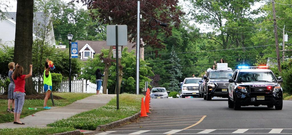 Photo of teachers and staff waving as 5th graders and families pass by during Grade 5 Clap Out Car Parade