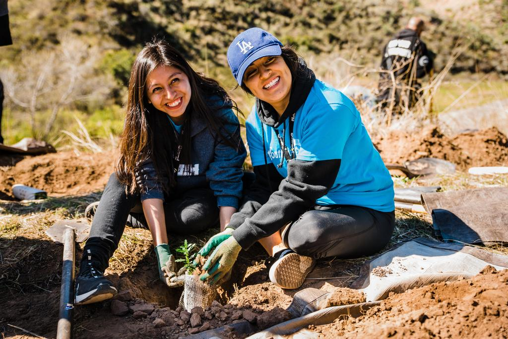 Two Lennox students smile while shoveling dirt on a plant