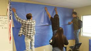 Students hang backdrop