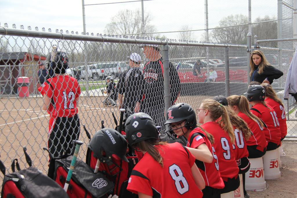 Softball players sitting on a bench