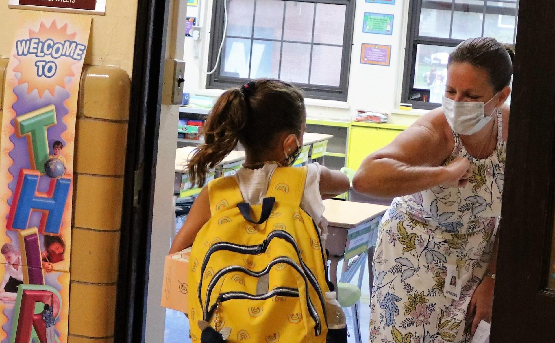 Photo of teacher with mask elbow bumping student with mask on first day of school
