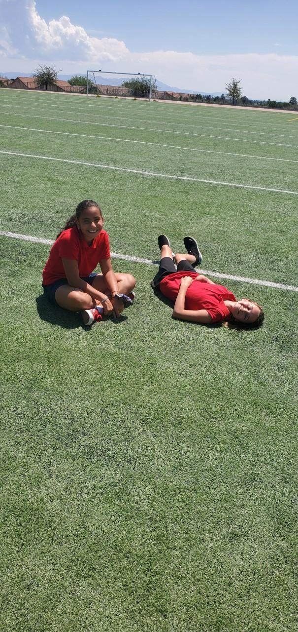 2 girls laying on the grass