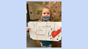 girl holding sign that says teachers are awesome