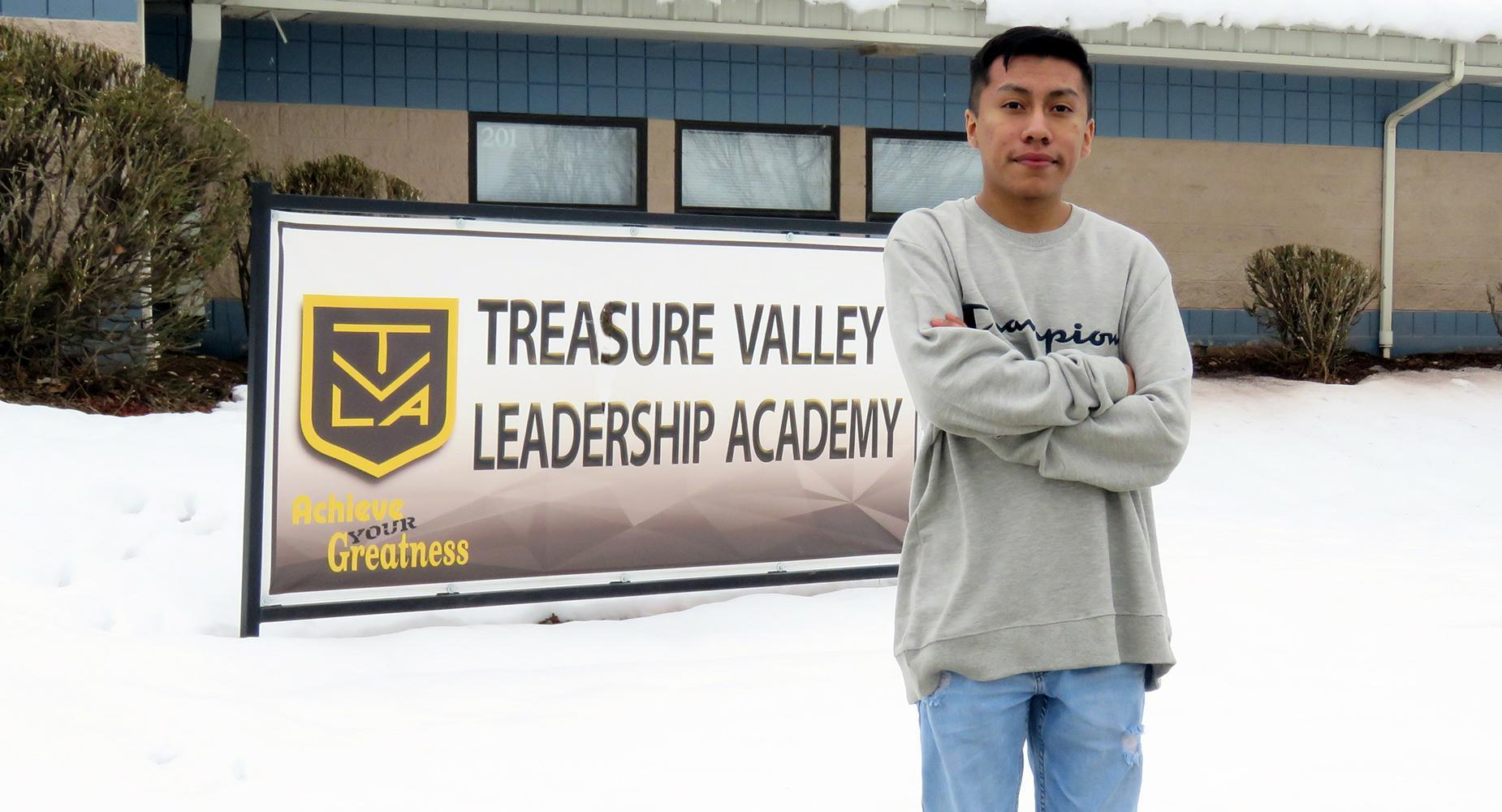 High school sophomore standing with his arms folded in front of TVLA banner outside the school.