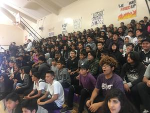 Students from Bridges Academy seated in the stands at a rally in the Bridges gym.