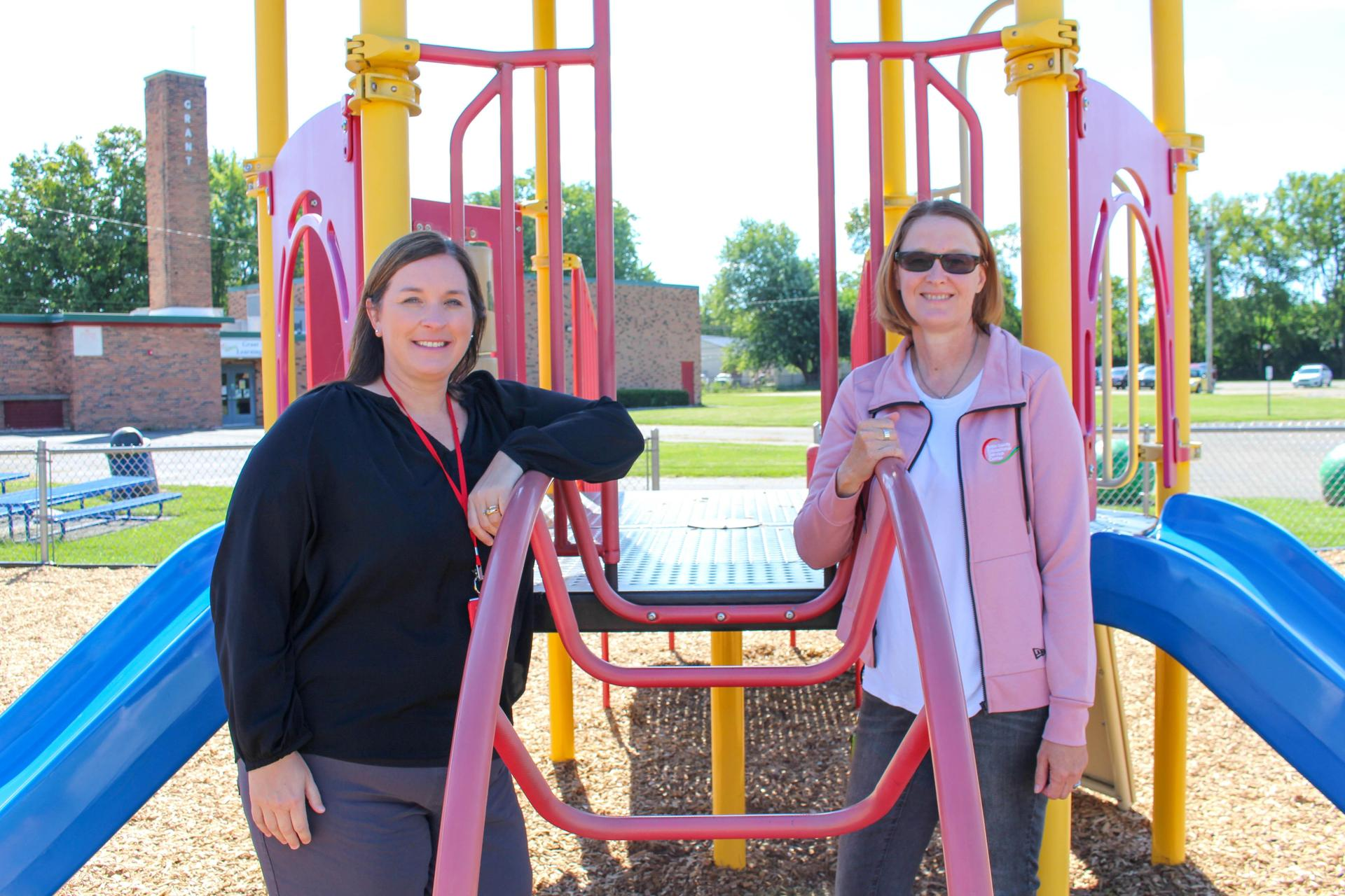 Child care specialists Kristin Gray and Donna Eisenbraun stand outside the Grant Early Learning Center
