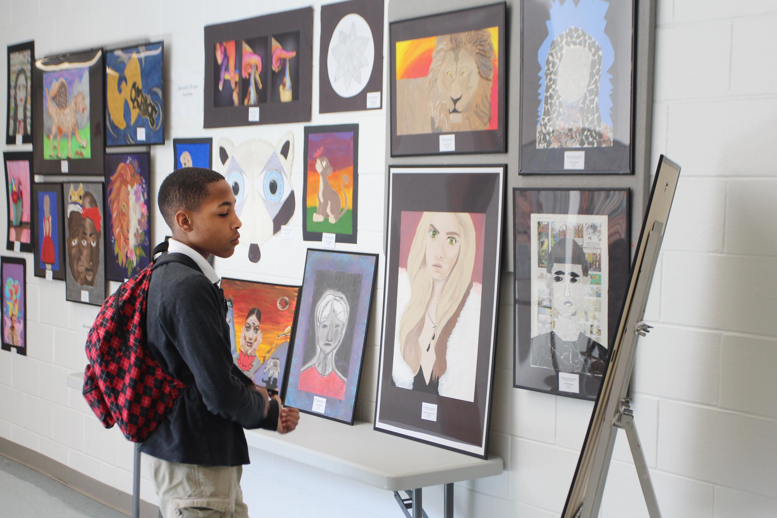 Student looking at art work on dispaly