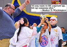 """If you want to lift yourself up, lift up someone else."" -Booker T. Washington Description: Cheering elementary children at a school pep rally showing off their hard won trophy"