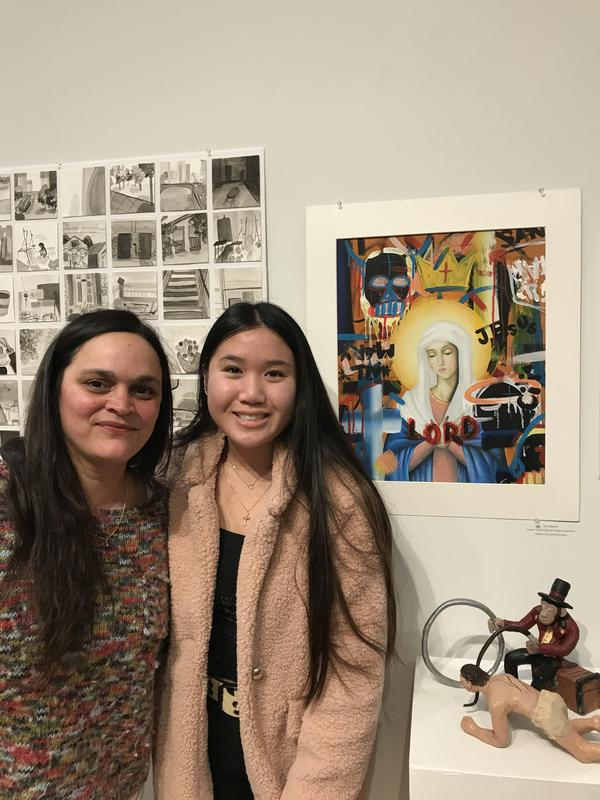 WOMAN AND TEEN STANDING IN FRONT OF PAINTING AT ART GALLERY