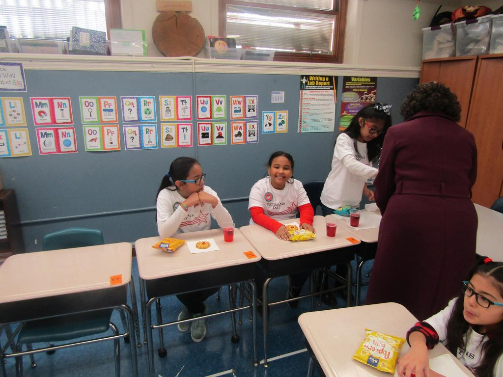 girls in a row enjoying their snacks at their desks