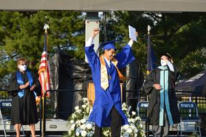 Graduate in blue gown poses after receiving his diploma