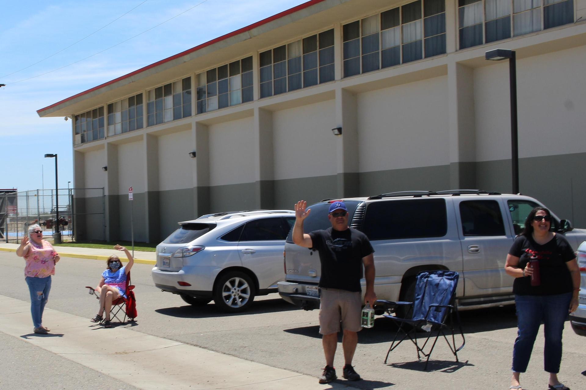 Teachers' Mary Freitas, Greta Knoublauch, John Henson, and Diana Starn waving at seniors