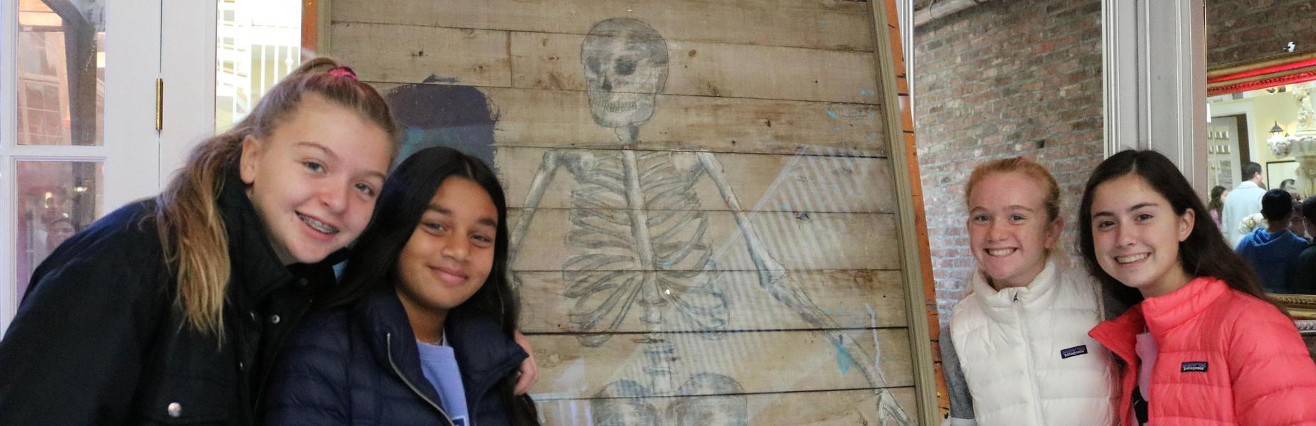RIS 8th grade art students pose in front Dudley, an original sketch by Westfield native Charles Addams during a visit to an exhibit of Addams' work.
