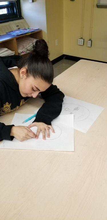 Student drawing a face during art class