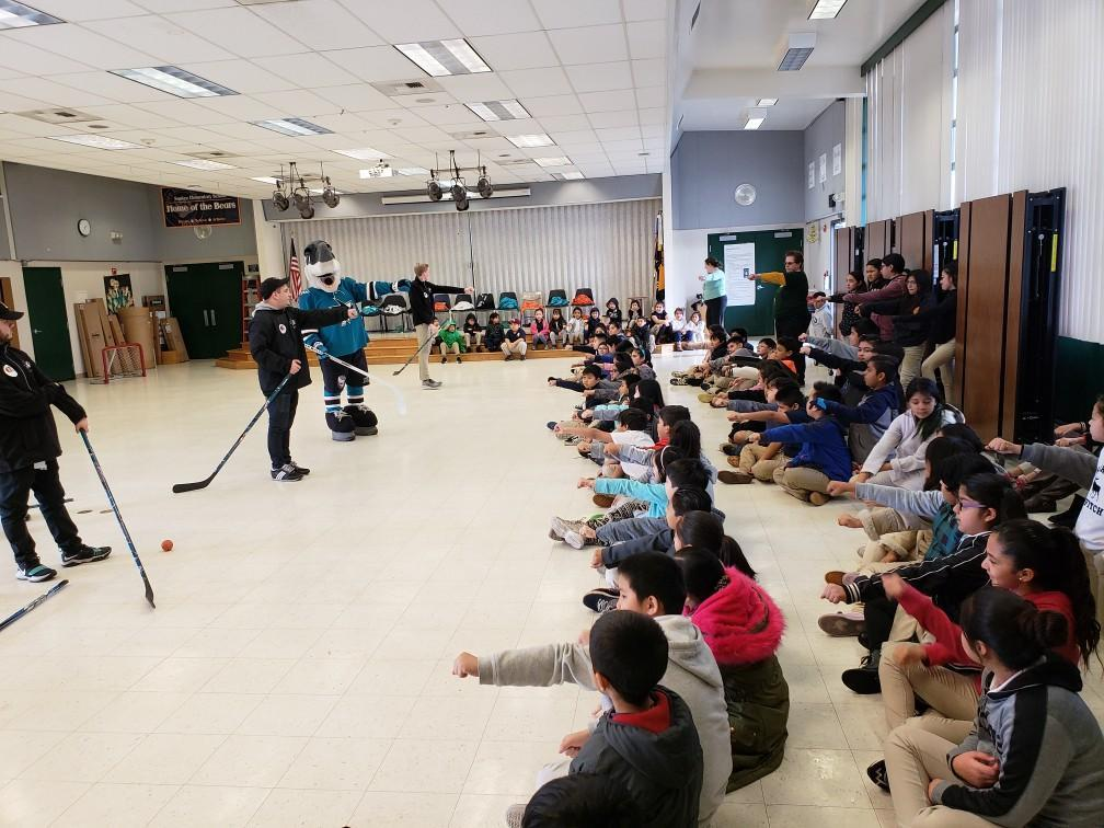 sharkey mascot and sharks players demonstrate how to use hockey stick