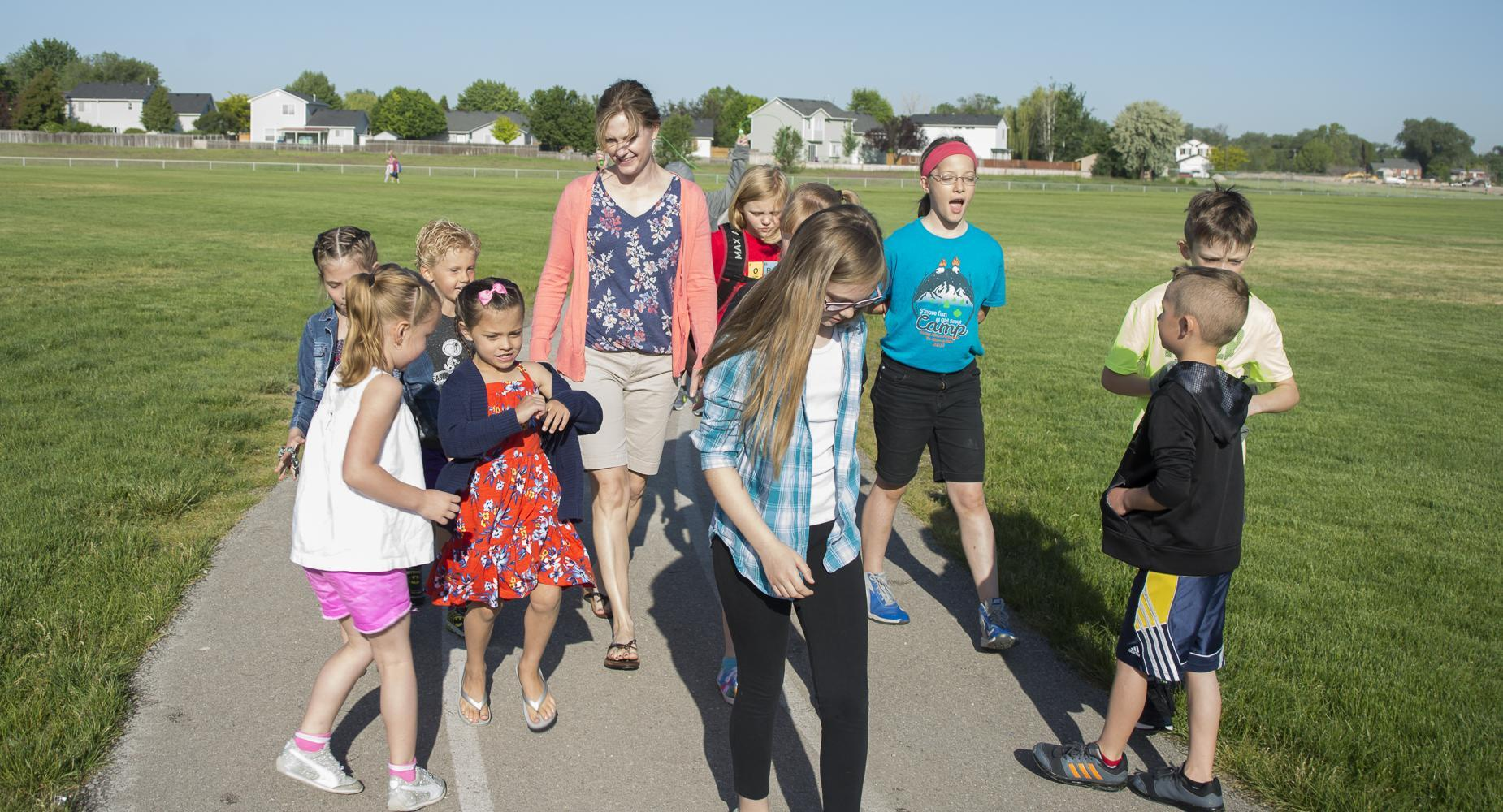 Principal Heather Yarbrough walks on the school track with kids